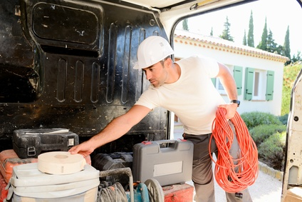 young electrician artisan taking tools out of professional truck van